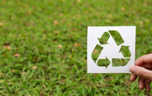 Logotipo de reciclagem em fundo de grama