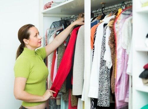 Mulher revisando as roupas do seu armário