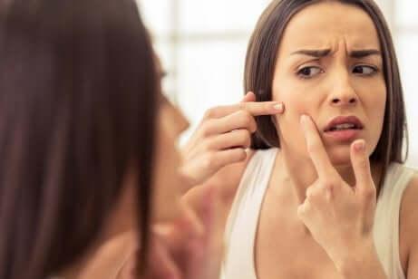 Tocar a face e as espinhas no rosto