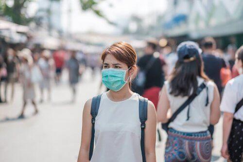 Mulher usando máscara na rua
