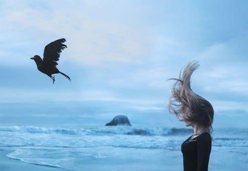 Mulher e corvo na praia