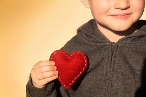 Criança segurando coração de pano