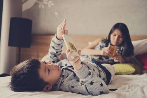Crianças usando eletrônicos na cama