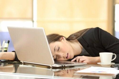 Mulher dormindo na mesa no trabalho