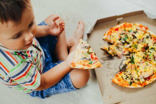 Menino comendo pizza