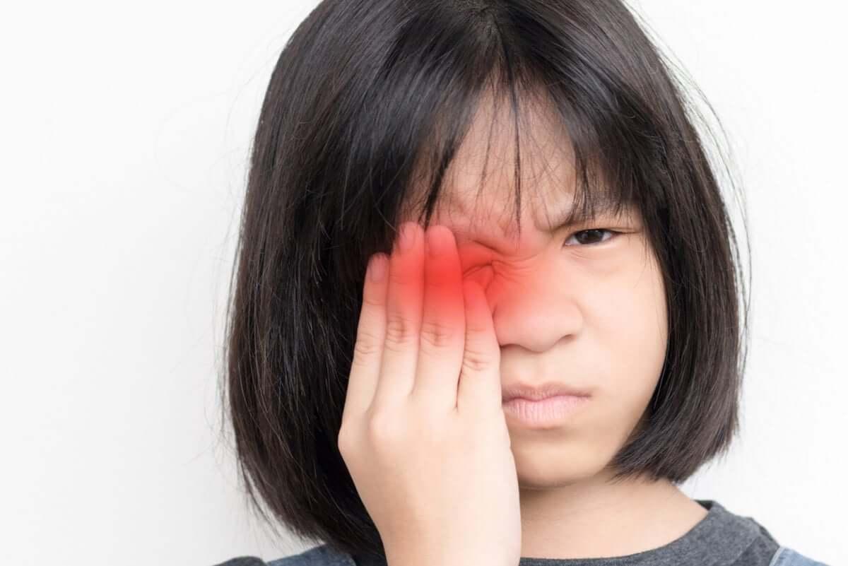 Menina com dor nos olhos