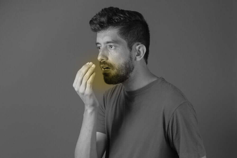 Homem sofrendo de halitose