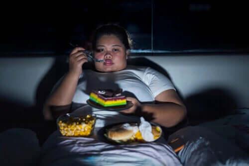 Mulher obesa comendo e vendo televisão