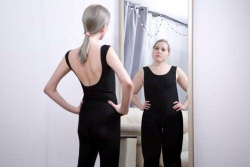 Mulher vendo sua imagem distorcida no espelho