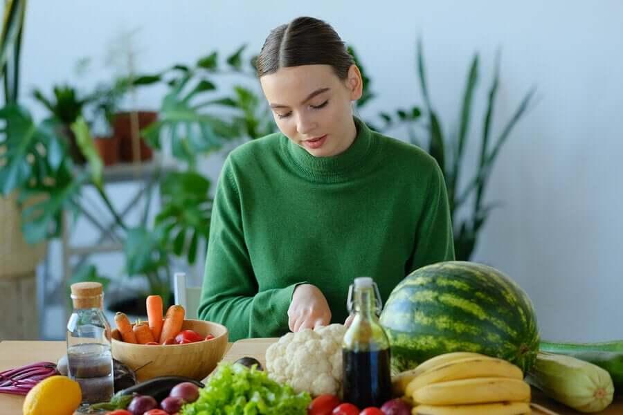 Mulher cortando frutas e verduras
