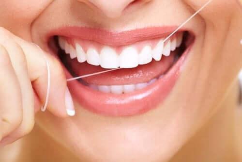 Mulher usando fio dental