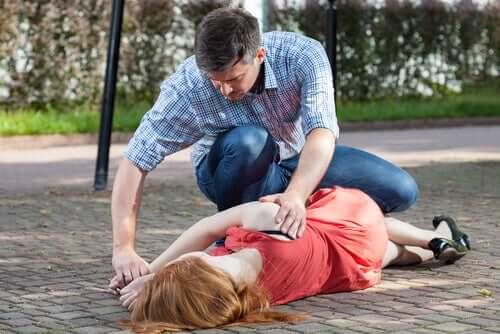 Homem ajudando mulher desmaiada