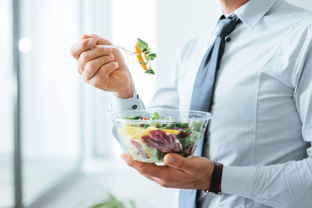 Homem comendo salada no trabalho
