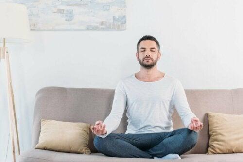 Homem meditando no sofá