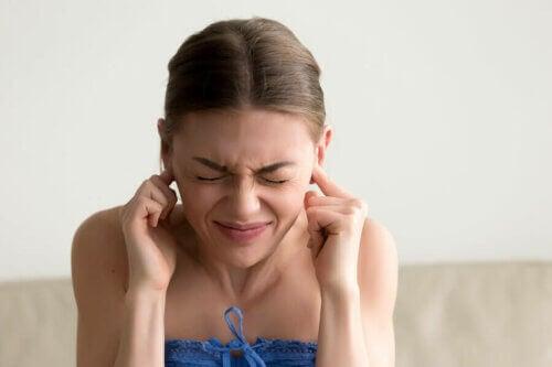 Mulher ouvindo zumbidos no ouvido