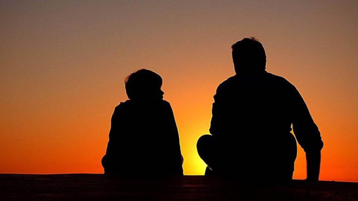 Pai e filho diante do pôr do sol