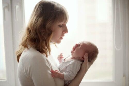 Bebê chorando no colo da mãe