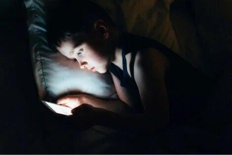 Criança com celular no escuro